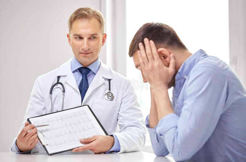 Doctor and patient with cardiogram on clipboard stock photo