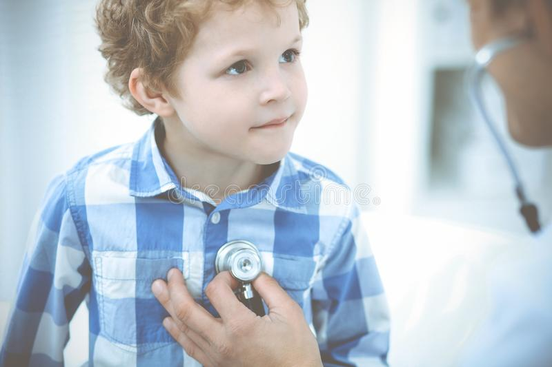 Doctor and patient child. Physician examining little boy. Regular medical visit in clinic. Medicine and health care stock photos