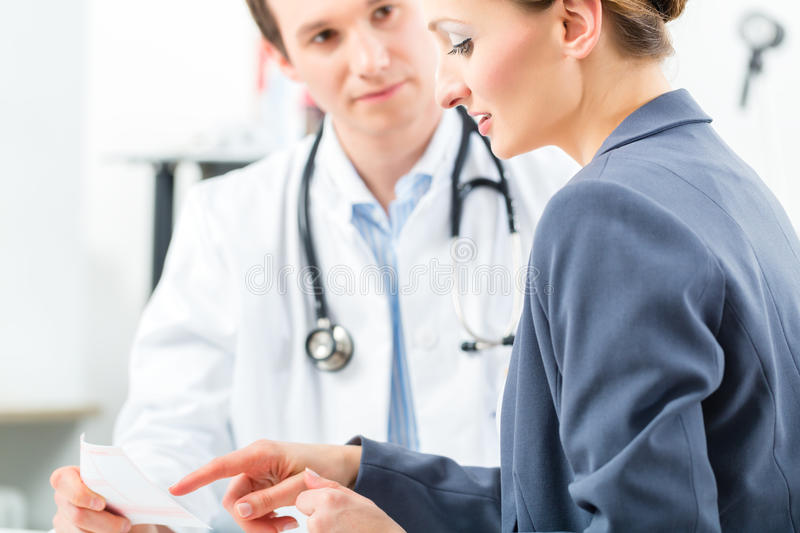 Doctor With Patient In Clinic Consulting Royalty Free Stock Image