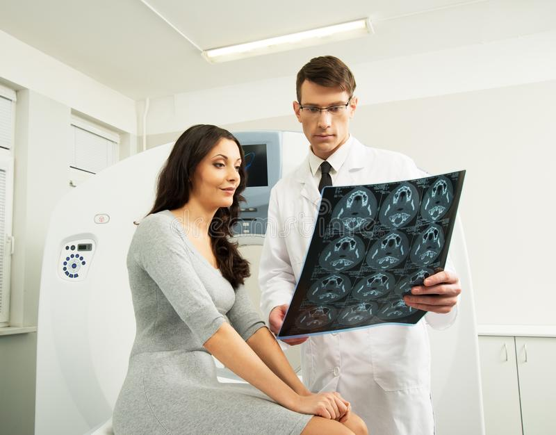 Doctor with patient at the computed tomography. Doctor with young women patient looking at the computed tomography results stock images
