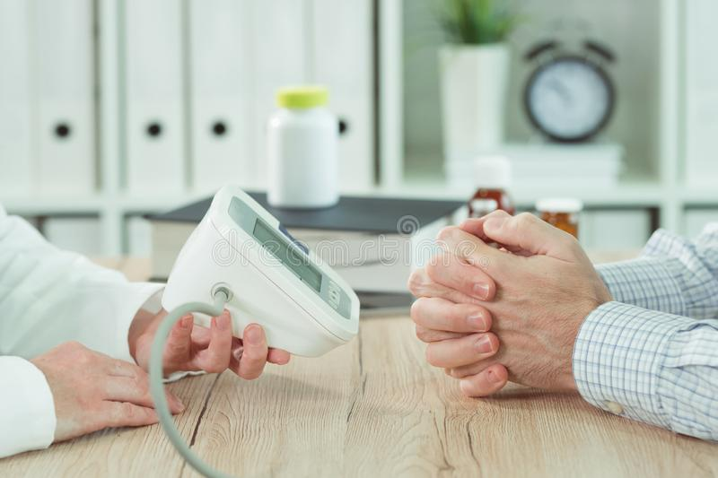 Doctor and patient with digital blood pressure monitor royalty free stock photo