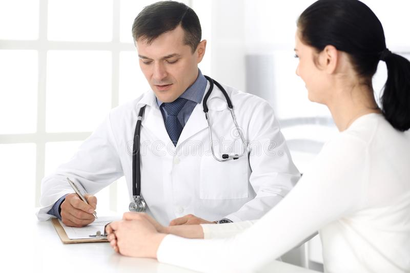 Doctor and patient discussing medical exam resoults at hospital office. Physician using clipboard for filling up royalty free stock photos
