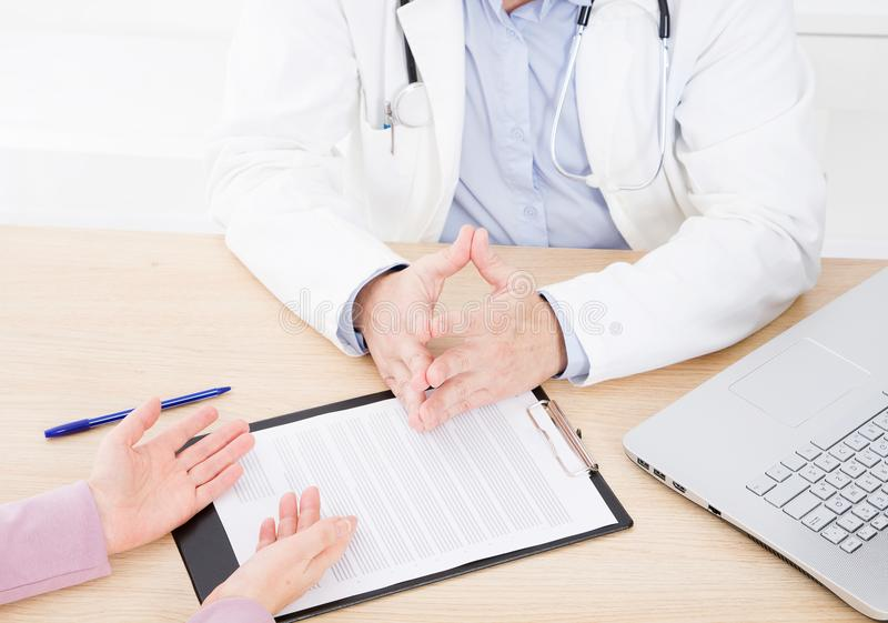 Doctor and patient are discussing something, just hands at the t. Able stock photos