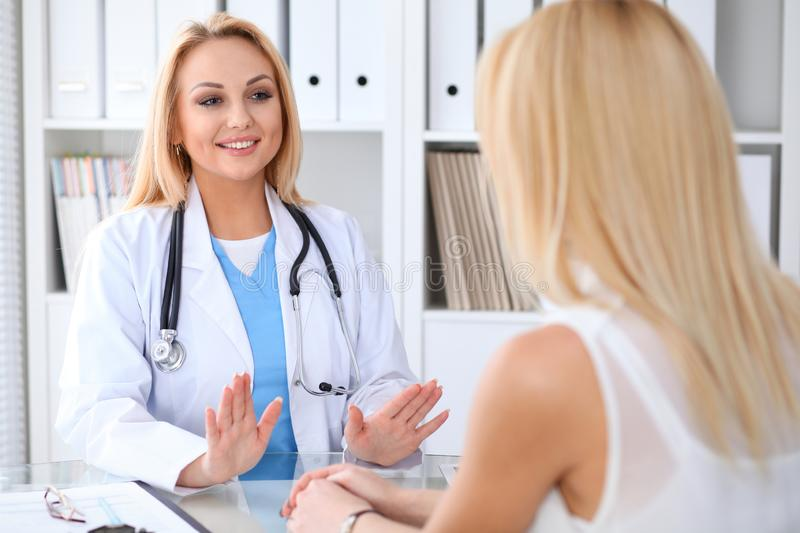 Doctor and patient discussing something while sitting at the table at hospital. Medicine and health care concept stock photo