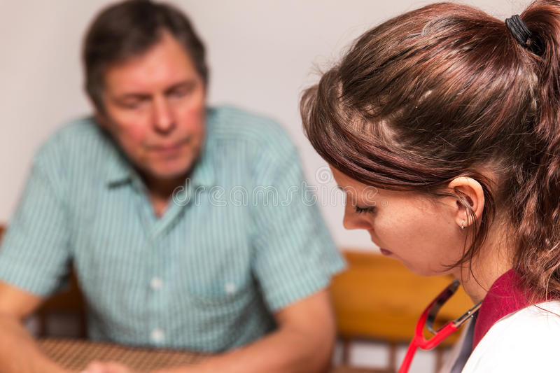 Doctor and patient having a conversation. Doctor and senior adult having a conversation royalty free stock photography