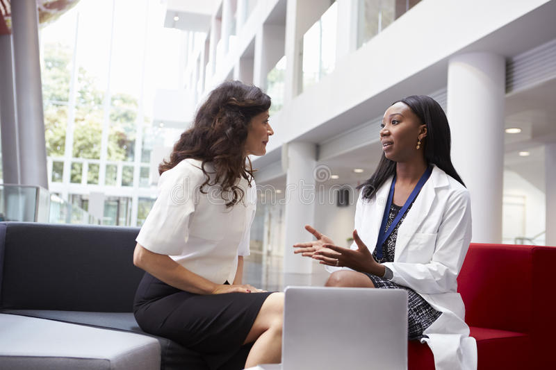 Doctor And Patient Having Meeting In Hospital Reception Area royalty free stock images