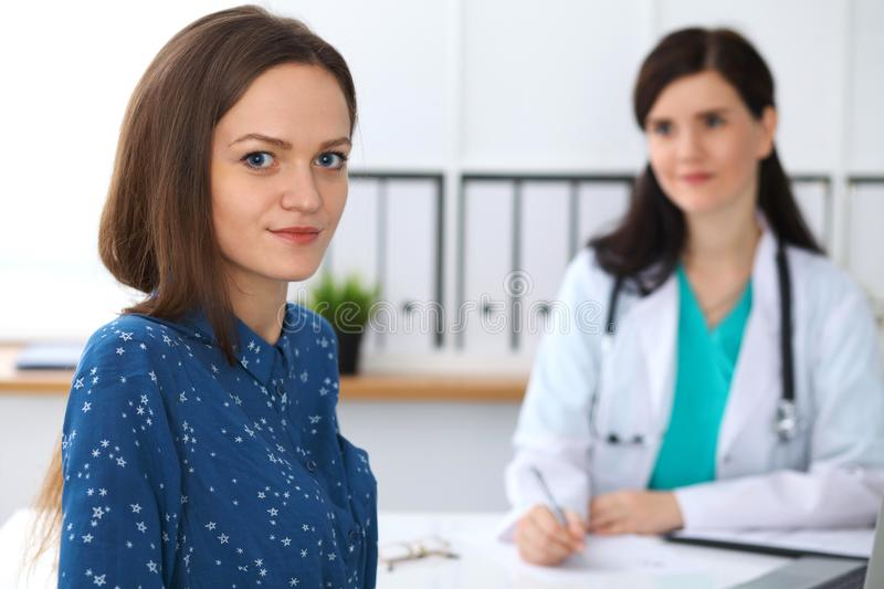 Doctor and patient having a talk while sitting at the desk. Focus on young beautiful woman looking at camera . Medicine. Doctor and patient having a talk while royalty free stock photography