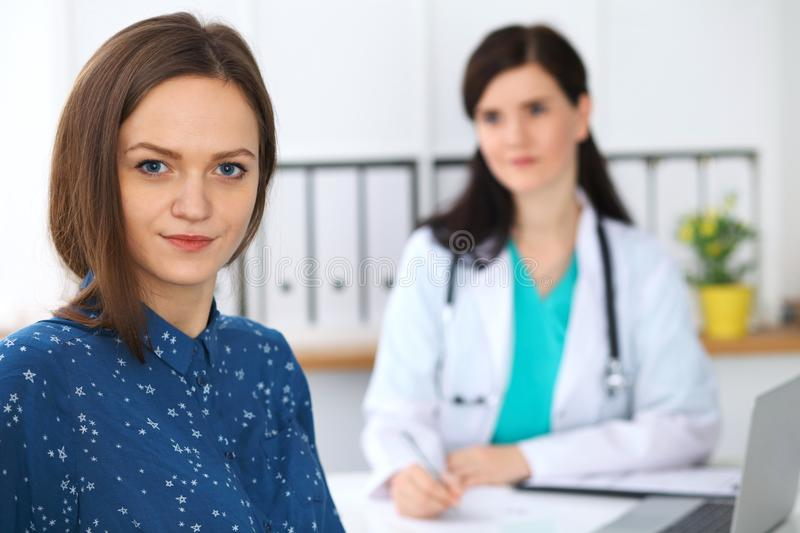 Doctor and patient having a talk while sitting at the desk. Focus on young beautiful woman looking at camera . Medicine. Doctor and patient having a talk while royalty free stock image