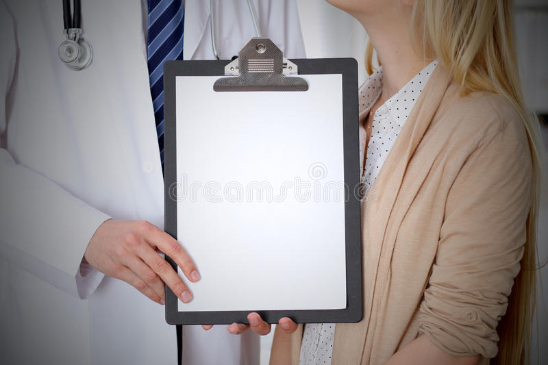 Doctor and patient holding clipboard free copy space. Medical ethics and trust concept.  stock images