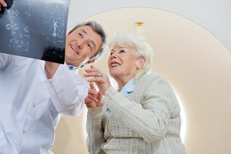 Doctor With Patient Looking At MRI X-ray royalty free stock photos