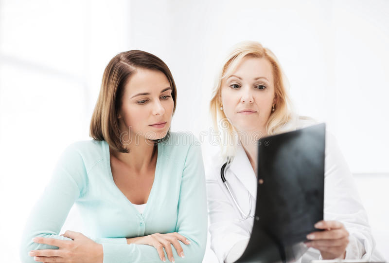 Doctor with patient looking at x-ray. Healthcare, medical and radiology concept - doctor with patient looking at x-ray stock images