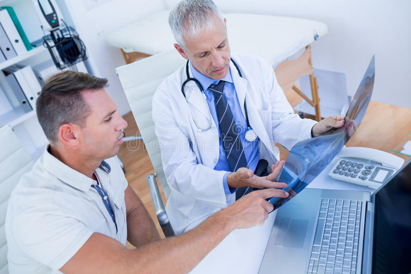 Doctor and patient looking at Xray stock photo