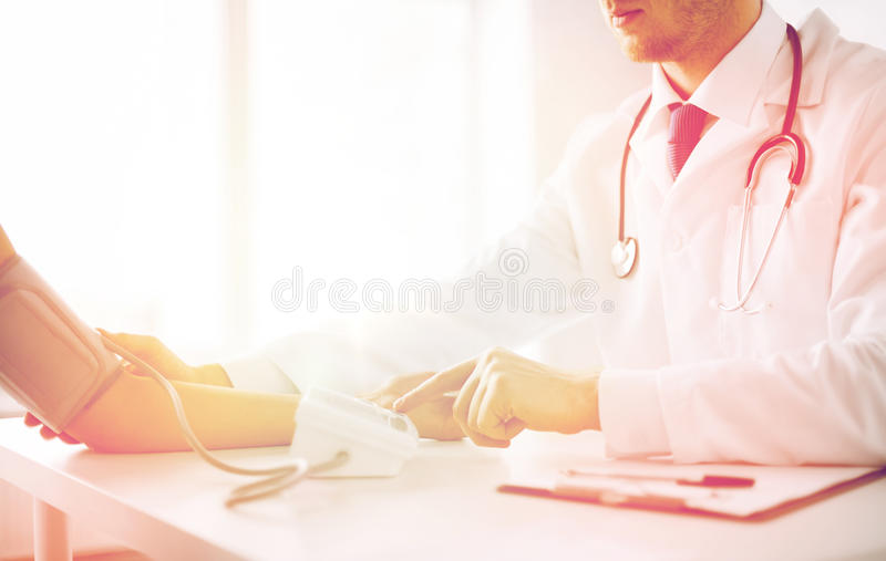 Doctor and patient measuring blood pressure stock images