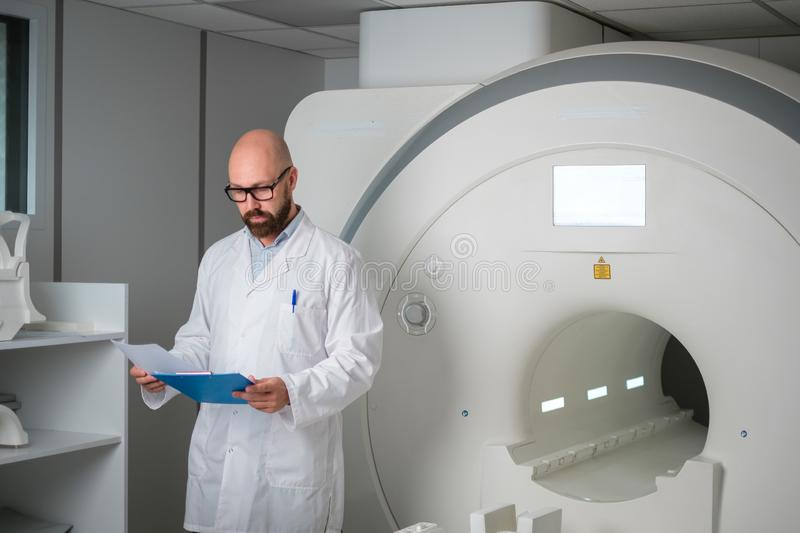 Doctor with a patient medical card near MRI scanner in a hospital royalty free stock image