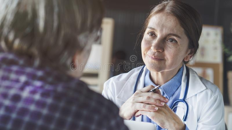 Doctor with patient in medical office stock image