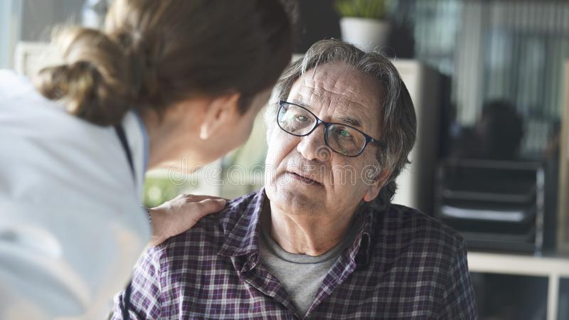Doctor with patient in medical office stock photos