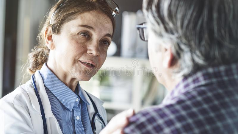 Doctor with patient in medical office royalty free stock images