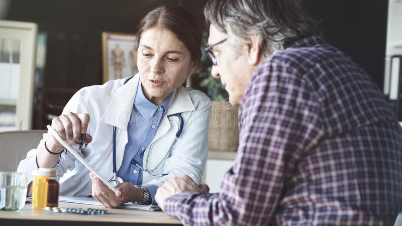Doctor with patient in medical office stock photo