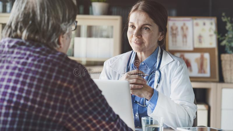 Doctor with patient in medical office royalty free stock photo