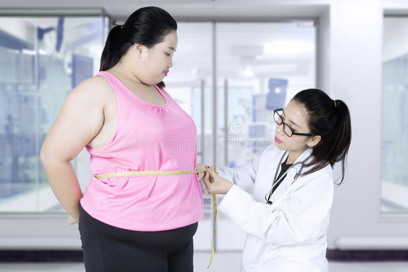 Doctor with a patient obesity in the clinic. Young female doctor looks serious while examining a patient obesity in the clinic royalty free stock images