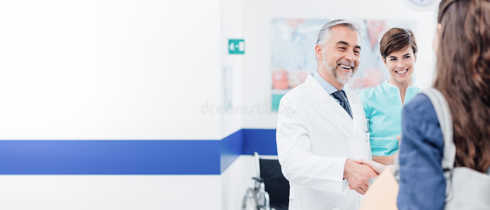 Doctor and patient shaking hands. Doctor and female patient meeting at the hospital and shaking hands, healthcare and medicine banner stock photo