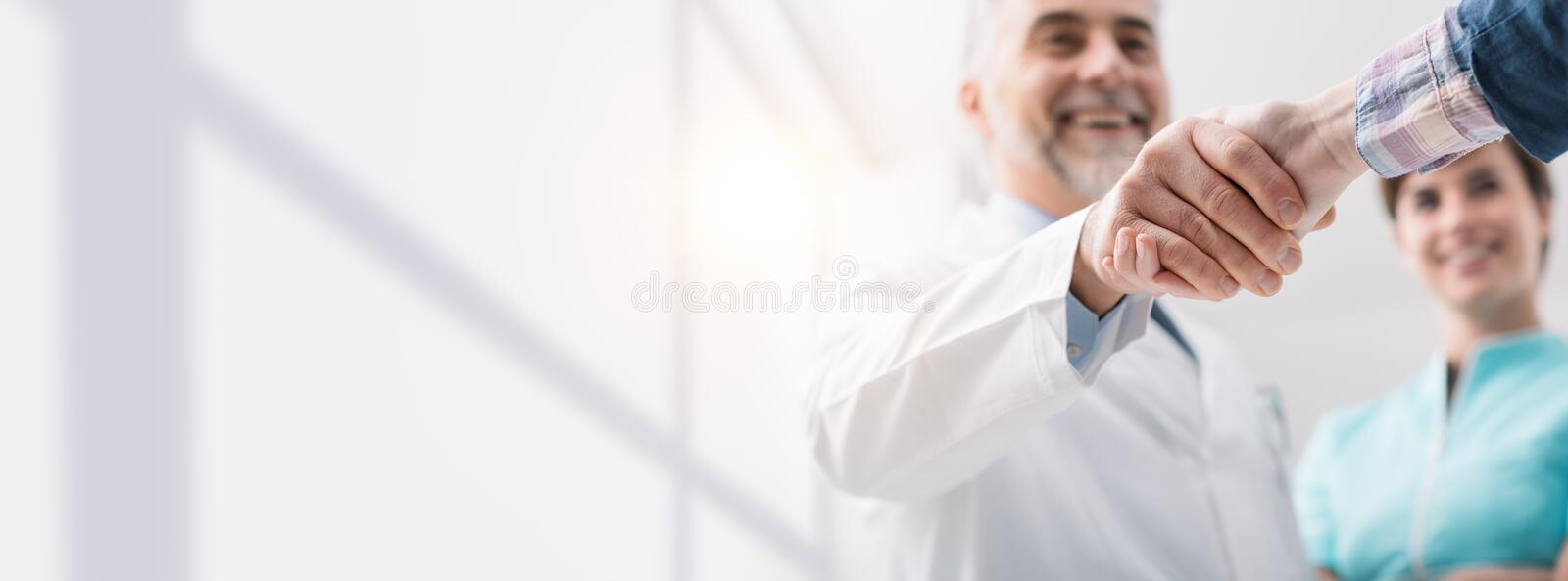 Doctor and patient shaking hands. Doctor and female patient meeting at the hospital and shaking hands, healthcare and medicine banner royalty free stock image