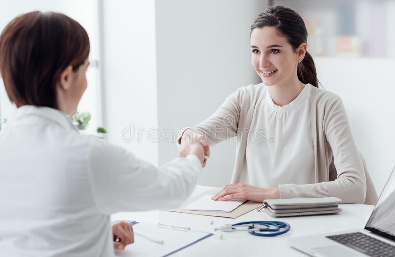 Doctor and patient shaking hands. Female doctor and young smiling patient in the office, they are shaking hands royalty free stock photo