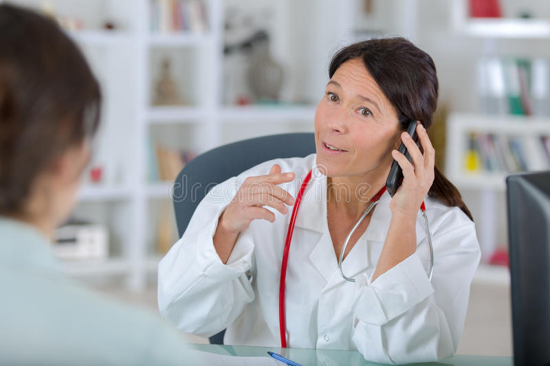 Doctor with patient and talking on phone. Doctor with patient and talking on the phone royalty free stock photography