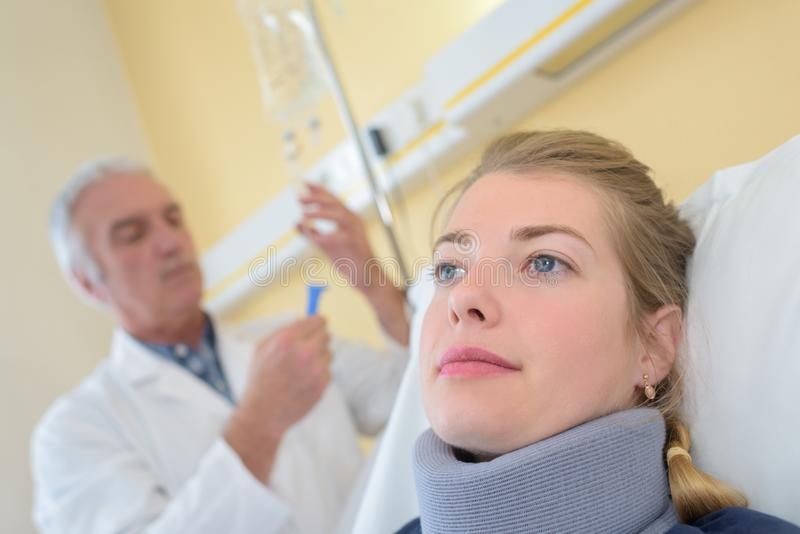 Doctor with patient wearing neck brace in hospital room. Portrait royalty free stock photography