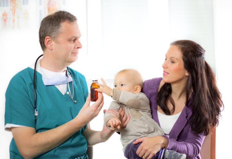 Doctor pediátrico que da la botella de píldoras a la madre con el bebé fotos de archivo libres de regalías
