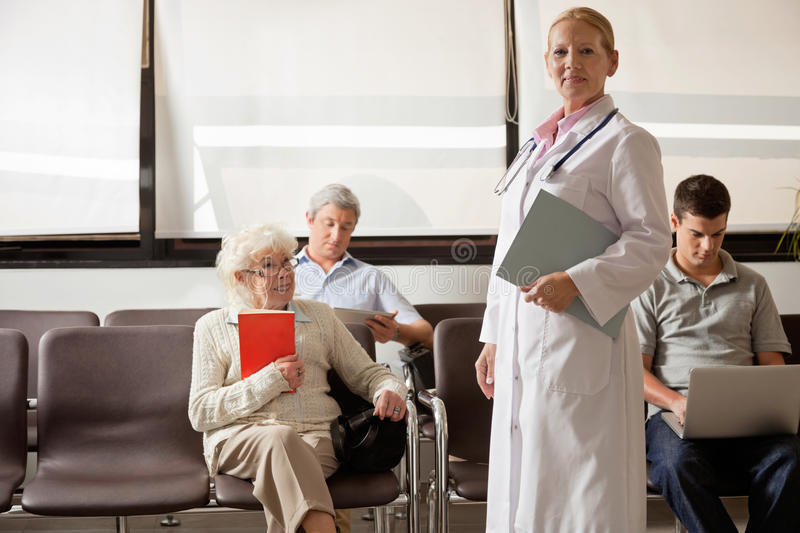 Doctor With People In Hospital Lobby. Portrait of female doctor holding file while people sitting in hospital lobby royalty free stock photo