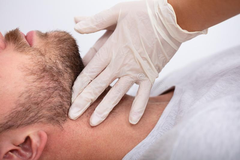 Doctor Performing Physical Exam Palpation Of The Thyroid Gland. Doctor`s Hand Wearing Gloves Performing Physical Exam Palpation Of The Thyroid Gland stock photos