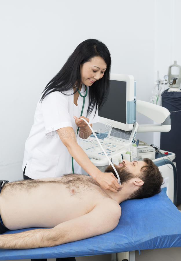 Doctor Performing Thyroid Ultrasound Test On Patient. Smiling female doctor performing thyroid ultrasound test on male patient in hospital stock photos