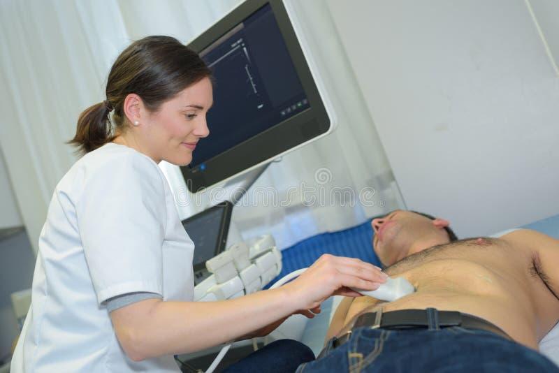 Doctor performing ultrasound on man`s abdomen. Ultrasound royalty free stock photos
