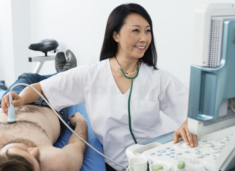 Doctor Performing Ultrasound Test On Patient. Happy mature doctor performing ultrasound test on male patient in hospital royalty free stock images