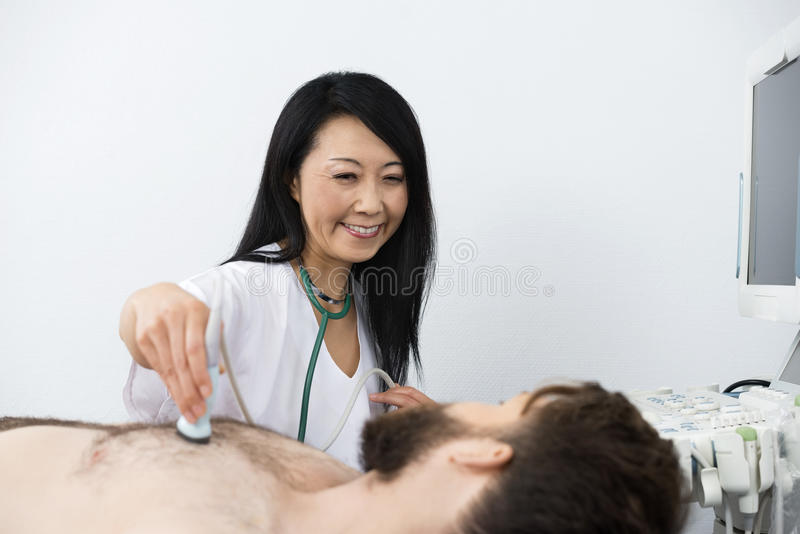 Doctor Performing Ultrasound Treatment On Patient. Smiling female doctor performing ultrasound treatment on male patient in hospital royalty free stock photo