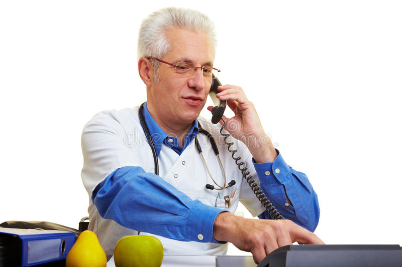 Doctor on the phone. Doctor sitting at his desk and making a phone call royalty free stock image