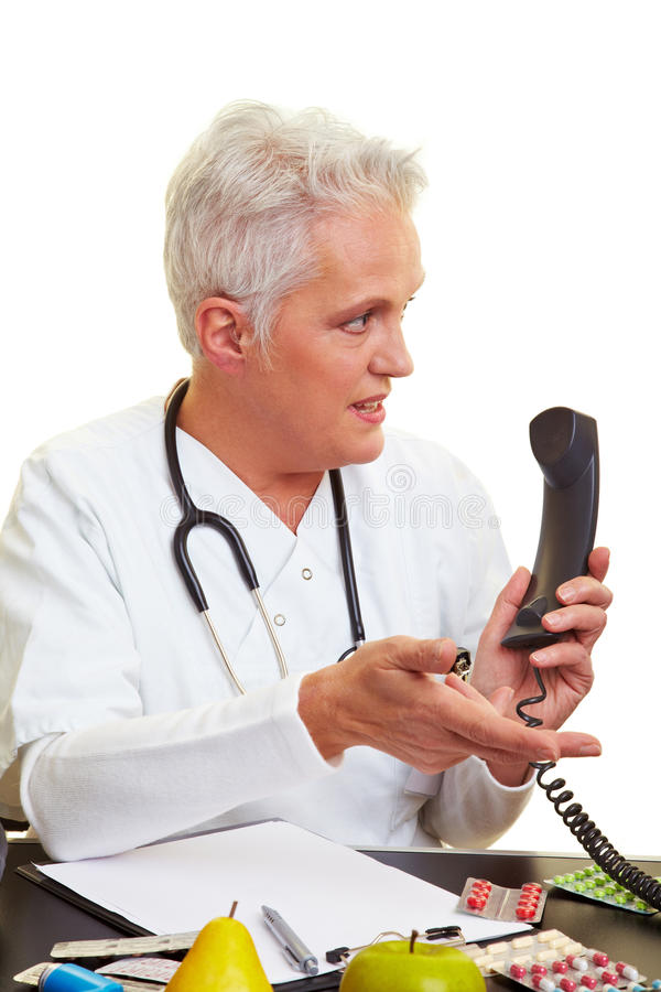 Doctor on the phone. Doctor sitting at his desk and making a phone call stock image