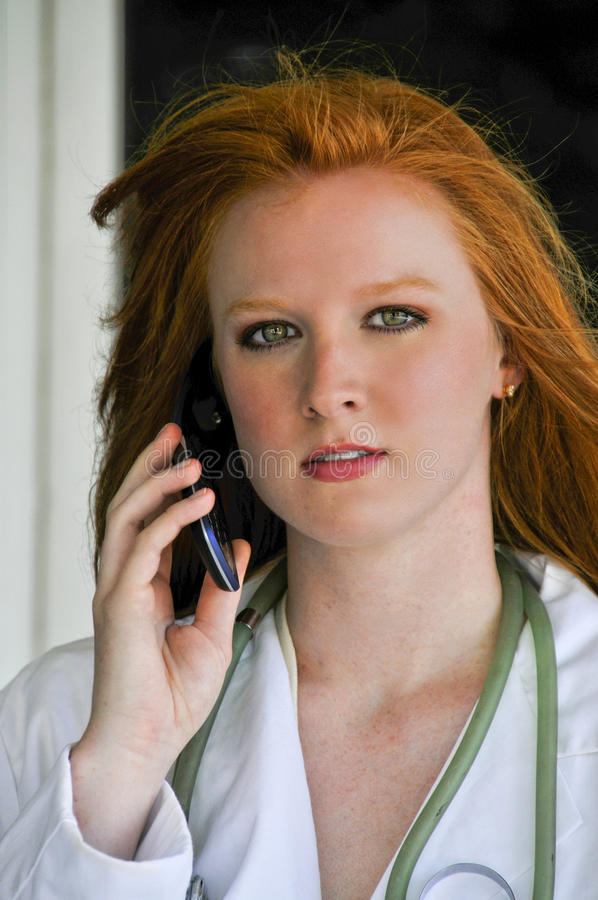 Doctor on the Phone. A beautiful young female doctor on the phone stock photos