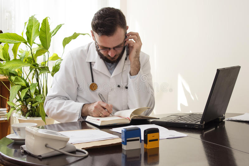 The doctor during a phone call saves appointment in the calendar. The doctor sits at his desk, taking notes talking on the phone stock images