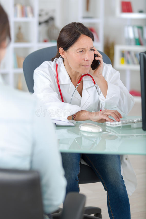 Doctor on phone calling analyzes centre with patient. Doctor on the phone calling analyzes centre with patient stock image