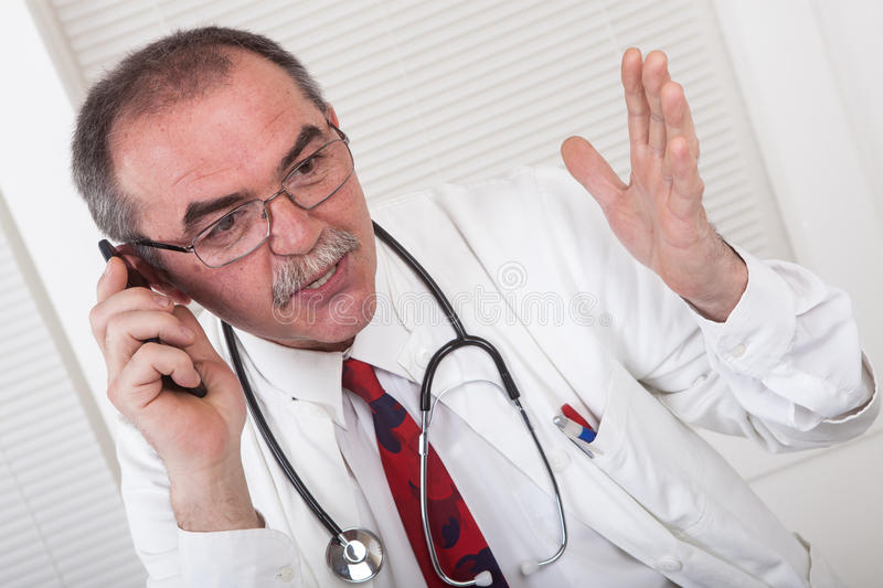Doctor on the phone. Caucasian senior doctor in office with mobile phone royalty free stock photography