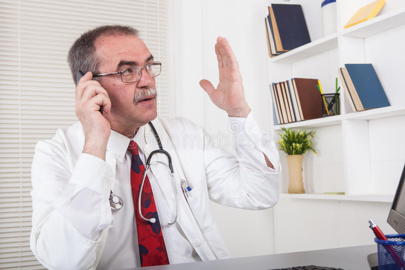 Doctor on the phone. Caucasian senior doctor in office with mobile phone stock photo