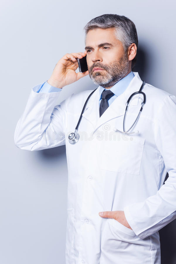 Doctor on the phone. Confident mature grey hair doctor talking on the mobile phone and looking away while standing against grey background royalty free stock images
