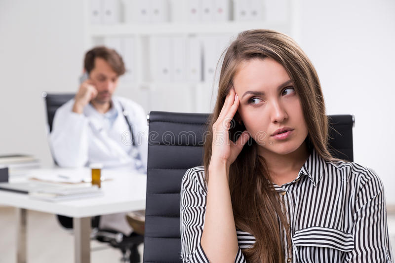 Doctor on phone. Doctor is having phone conversation while patien looks bored and waiting for him to finish examination stock image