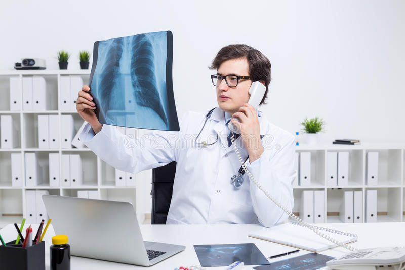 Doctor on phone holding x-ray. Young caucasian doctor at office desk looking at an x-ray and talking on the phone royalty free stock photography