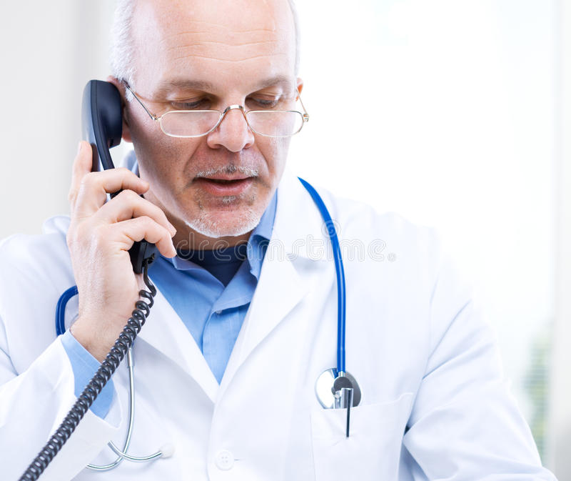 Doctor on the phone. Portrait of a Doctor talking on the phone royalty free stock photography