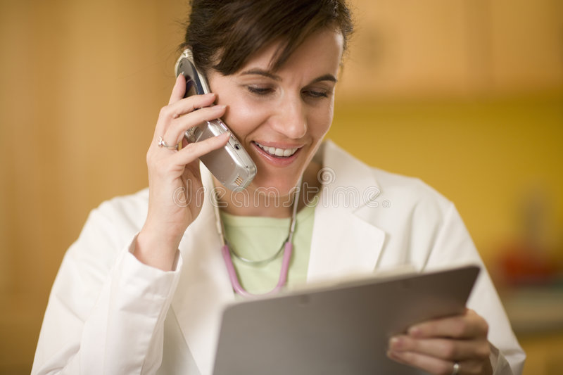 Doctor on phone reading medical records. Woman doctor talking on cell phone and looking at a medical chart stock photos