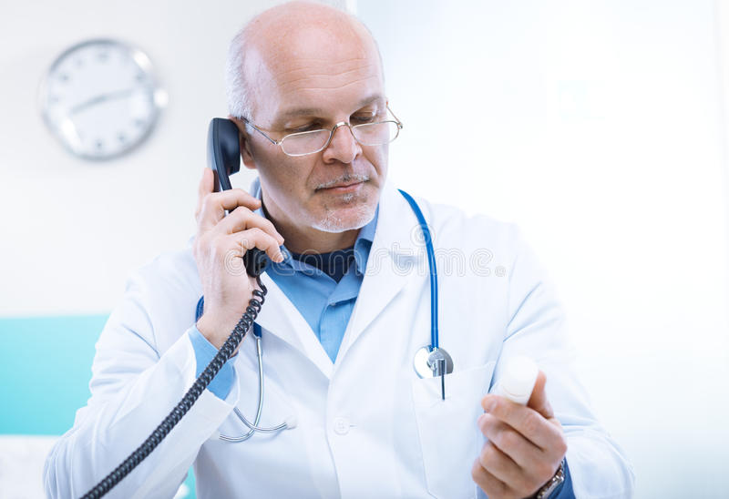 Doctor on the phone. Doctor talking on the phone and looking at medicine's bottle royalty free stock photos