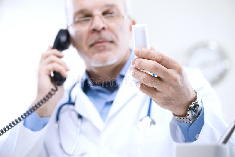 Doctor on the phone. Doctor talking on the phone and looking at medicine's bottle stock images